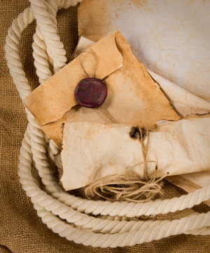 composition with an old envelope, parchment and rope