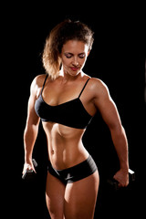 Sporty muscular woman with two dumbbells
