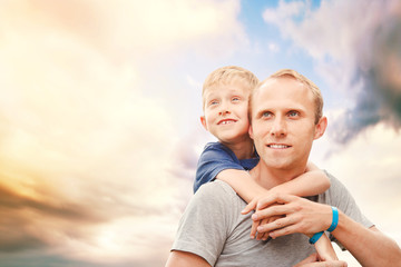 Father with son portrait on the sky background
