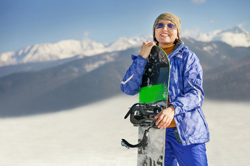 Happy smiling woman with snowboard on the mountain hill