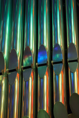 Colorful shining organ tubes in church, vertical photo