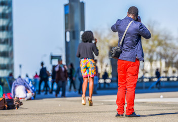 A young man in bright red trousers taking a photo