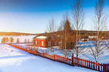 House at lake in Scandinavia at sunset
