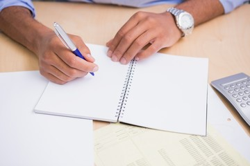 Hand writing documents at desk