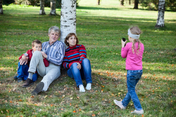 Family sitting under tree in park when girl makes picture phone