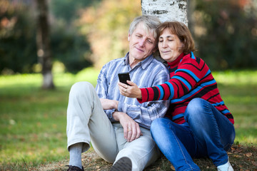 Mature couple sitting together and making selfie with phone park