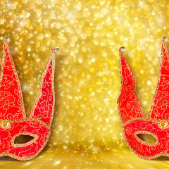 Carnival red mask on gold abstract background with bokeh effect