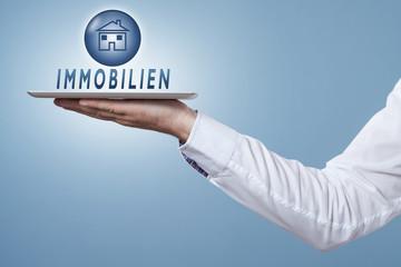 Hand hält Tablet darüber ein Symbol Immobilien