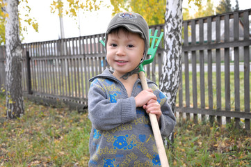Boy portrait with rake smiling