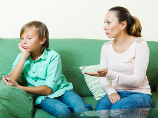 serious middle-aged mother scolding teenage son