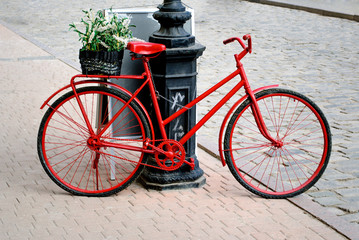 a bicycle is red with the small basket of colors