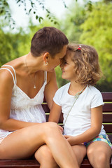 Happy mother and little daughter sitting outdoors