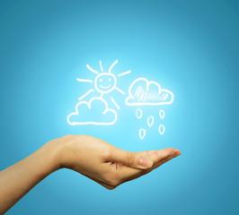 woman's hand holding cloud sun rain icons blue background