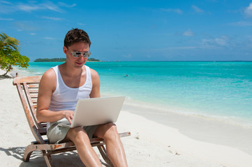 Man with sunglasses relaxing at the beach with laptop