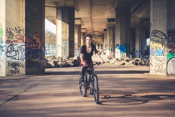 young beautiful punk dark girl riding bike