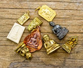 many small buddha image used as amulets on wood background