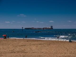 Sandstrand mit Blick auf Festung im Meer