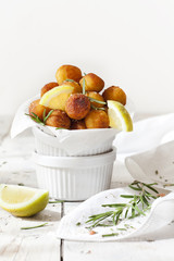 balls of fried potatoes with lemon slice and rosemary on table