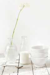 tuberose flower on glass, three bowls and bottle of milk