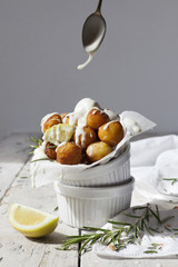 balls of fried potatoes with dripping yogurt sauce from spoon