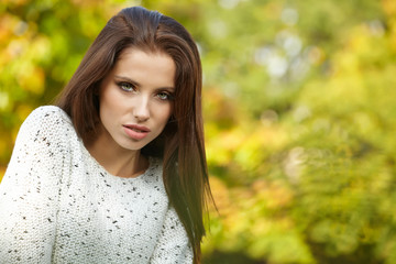 Beautiful fashion woman standing in a park in autumn