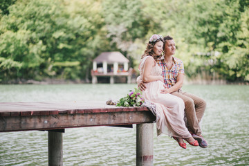 Young pregnant woman with her husband sitting on berth near lake
