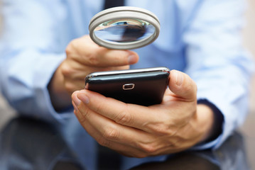 Businessman using mobile smart phone with magnifying glass . Pho