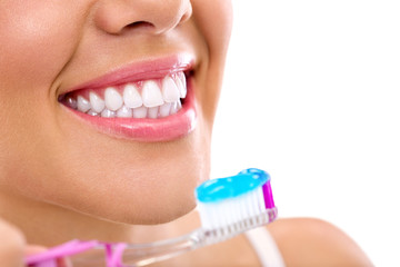 woman with healthy teeth holding a tooth-brush