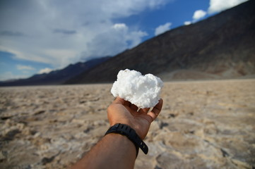 A piece of white salt from the Death Valley in the outstretched hand on a background of the cloudy sky over the mountain