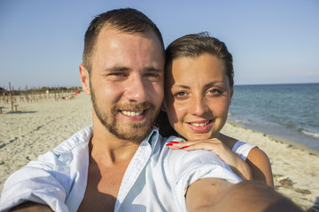 Happy couple taking a photo on a beach