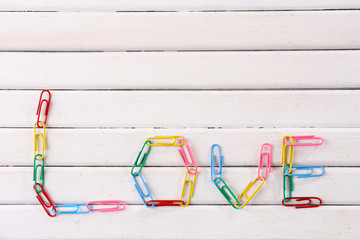 Love word formed with colorful clips on wooden background