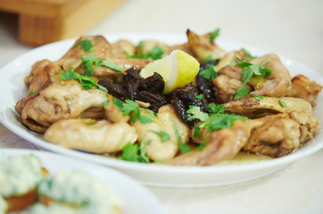 chicken wings with prunes, lemon and parsley