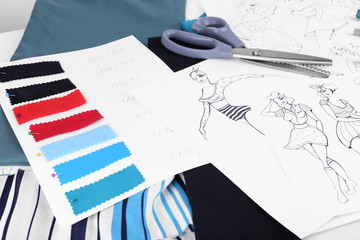 Sketches of clothes and fabric samples on table