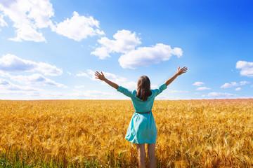 Woman raising arms enjoying sunlight in field