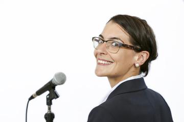 Sucssesful businesswomen keynote speaker in front of microphone