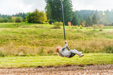 Cute toddler boy playing on a chain swing