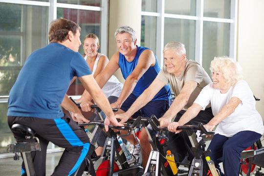 Trainer mit Gruppe Senioren beim Spinning