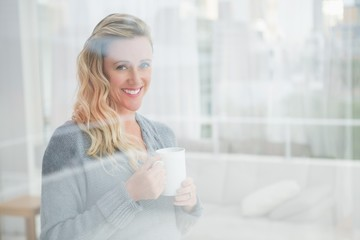 Smiling pretty blonde holding coffee