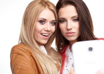 portrait of two beautiful girls making selfies at studio