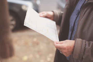 Old woman reading map in the street