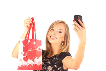 Beautiful girl with shopping bags taking selfie with phone