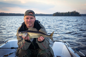Happy angler with autumn walleye fish