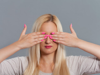 Studio shot of young woman with her hands covering eyes.