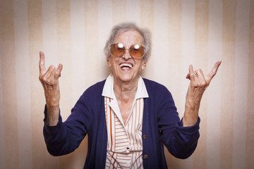cool elder lady making rock on sign Wall mural