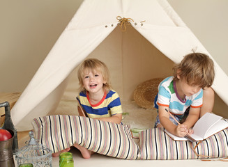 Children playing at home indoors with a teepee tent
