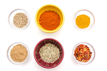 Bowls with spices viewed from above on white background