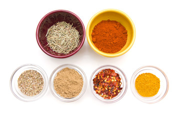 Spices in bowls seen from above on white background