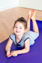 Happy child dooing sports exercises on mat.