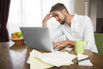 Frustrated male trying to do his taxes at home