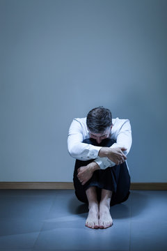 Depressed young businessman sitting on the floor
